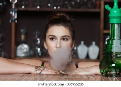 Beautiful girl smoking a hookah. Beautiful young woman inhaling hookah.Girl smoking in nightclub