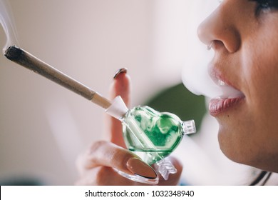 Beautiful girl smoking weed out of a glass joint pipe bubbler