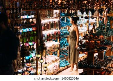 Beautiful girl in a souvenir shop in Morocco. Girl chooses a souvenir Oriental shop. Street shop. Moroccan Souvenirs. Oriental bazaar. Moroccan Bazaar. Tourist shop. Turkish Bazaar