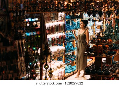 Beautiful girl in a souvenir shop in Turkey. Girl chooses a souvenir Oriental shop. Street shop. Turkish Souvenirs. Oriental bazaar. Turkish Bazaar. Tourist shop. Moroccan Bazaar.