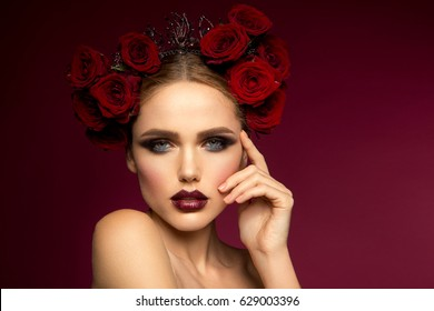 Beautiful girl. Spanish style. Red roses. Colored make up