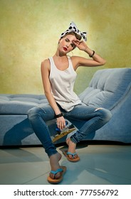 Beautiful girl with a spatula sits on the couch near the plastered wall