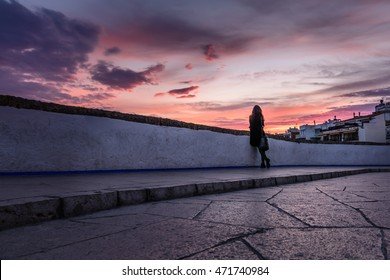 Beautiful girl and spectacular sky. Young elegant woman watching the sun go down over city.