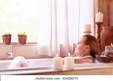 Beautiful girl spending time in the spa hotel, relaxing in the nice bath with foam, looking in the window, healthy treatment and enjoyment