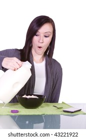 Beautiful Girl Spilling Milk while Trying to Pour it to the Cereal Bowl