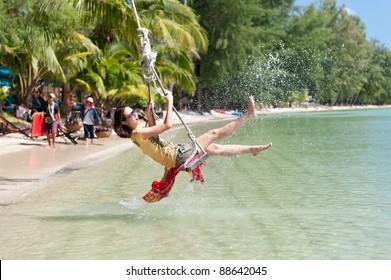Beautiful girl splashing water while playing swing at the sea