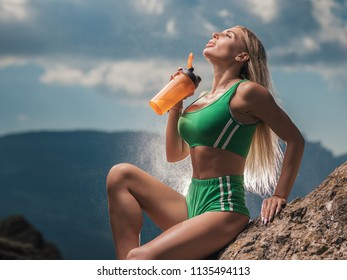 Beautiful Girl in sport clothes Drinking water after workout outdoor. Young Sexy Woman in sportswear drinks during Sports Training in nature.