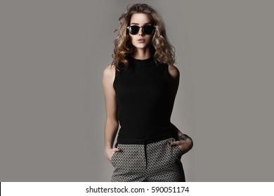 Beautiful girl with a sports figure. Stylish portrait of a pretty girl in sunglasses. Studio horizontal photo.