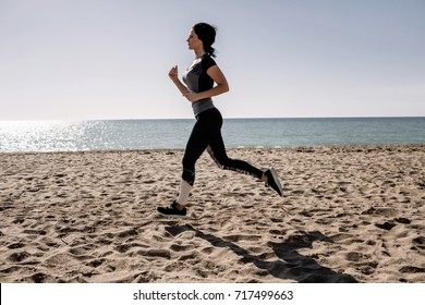 beautiful girl with sports forms sports on the beach, drinking water, jumping, running, doing different exercises