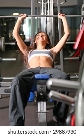 Beautiful girl in sports to a hall carries out exercise with a bar