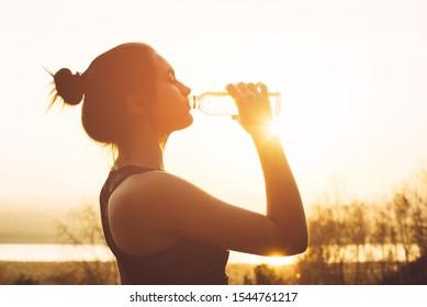 Beautiful girl in sportswear drinks water from a bottle at sunset - Shutterstock ID 1544761217