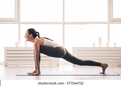 Beautiful girl in sportswear is smiling while doing yoga on yoga mat in sports hall