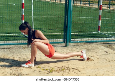 Beautiful girl sportswoman exercising on a sunny morning at the stadium