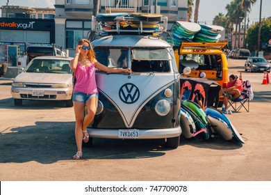 Beautiful girl standing by the VW hippy with surf boards in Los Angeles. USA. April 10, 2017