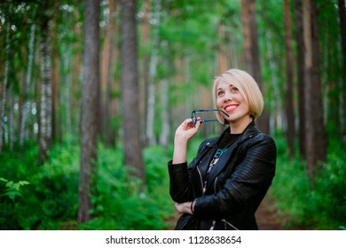Beautiful girl standing in the forest taking off her glasses enjoying the forest