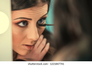 Beautiful girl standing in front of the mirror and applied makeup