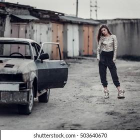 beautiful girl standing near old car