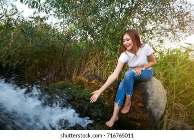 Beautiful girl standing near waterfall at sunset. Attractive slender tanned young brunette girl bathes in a small waterfall