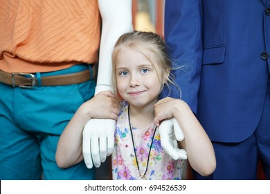 Beautiful girl is standing next to a dummy