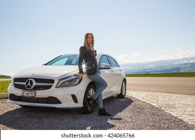 Beautiful girl standing next to the white Mercedes parked on the side of the road in Switzerland