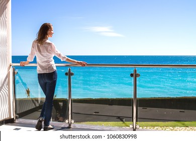 The beautiful girl standing on a balcony of apartments looking at the seaside.
