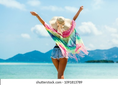 Beautiful girl is standing on the beach by the sea, wearing a pareo straw hat sunglasses, hands in the side gesture of freedom, summer vacation travel, a sense of joy