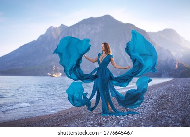 A beautiful girl standing on the beach in a long flying blue dress with a deep neckline and slits against the background of mountains, the sea, an ancient ship and the evening sky