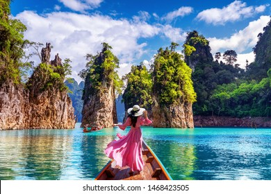 Beautiful girl standing on the boat and looking to mountains in Ratchaprapha Dam at Khao Sok National Park, Surat Thani Province, Thailand.