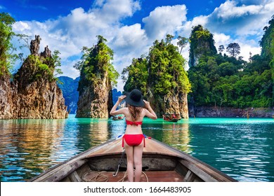 Beautiful girl standing on the boat in Ratchaprapha Dam at Khao Sok National Park, Surat Thani Province, Thailand.