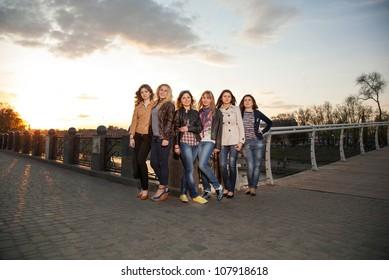Beautiful girl standing on the bridge at sunset