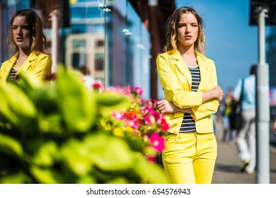 Beautiful girl is standing on the flowers at the city