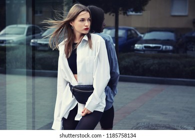 Beautiful girl standing at shopwindow at the street