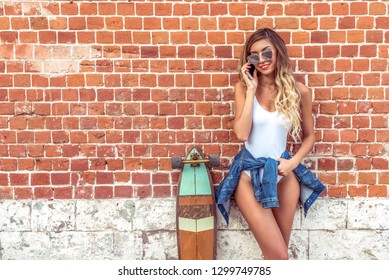 A beautiful girl standing in summer by brick wall. Woman In white body bathing suit, in her hand smartphone happy is talking and smiling. Board for skateboarding, longboard. Free space for text.