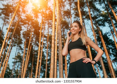 Beautiful girl standing in a summer forest park. Phone calls happy smiling. In sportswear jogging in the morning. Free space for text. Camping is a sport.