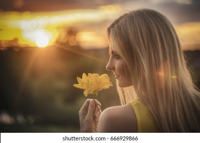 A beautiful girl standing in the sunset with flowers in her arms