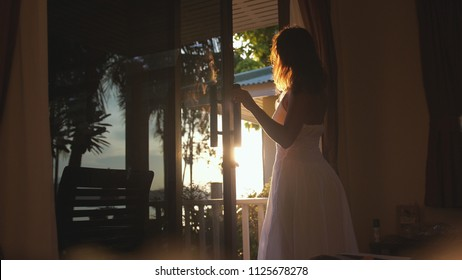 Beautiful girl stands in the doorway in the early morning during sunrise with lens flare effects