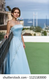A beautiful girl stands in a long blue dress