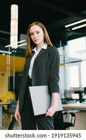 A beautiful girl stands in a modern office with a laptop in her hands. A spacious office with glass partitions and doors, yellow and black walls. Podcaster. Freelancer. - Shutterstock ID 1919135945
