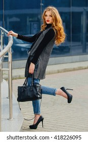 Beautiful girl stands near the business center, with her bag and long heels.