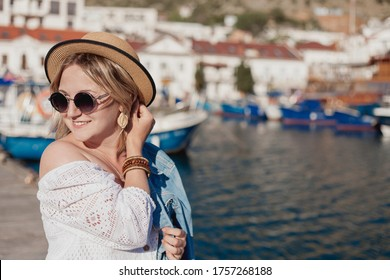 beautiful girl stands on the promenade near the sea, yachts, mountains, fresh air on vacation. - image