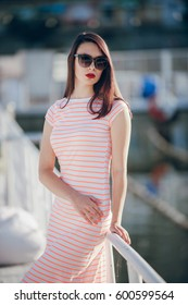 beautiful girl stands on the sunny pier
