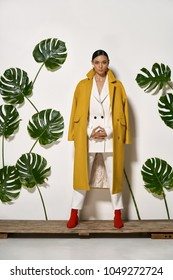 Beautiful girl stands on a wooden platform in a studio on a background of a white wall with big green leaves. She wears a white pantsuit, mustard coat and red boots. Woman looks into a camera.