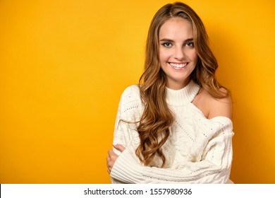 Beautiful girl stands on a yellow background in a white sweater hugging herself over the shoulders and smiling.