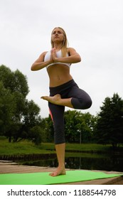 A beautiful girl stands in the pose of Vrikshasana. Yoga.