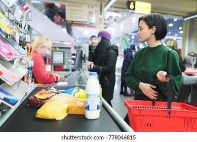 A beautiful girl stands at the supermarket and waits for a queue. The amount pays for purchases at the supermarket's cash desk.