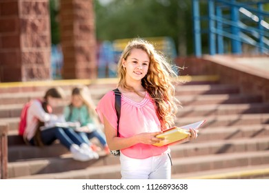 beautiful girl stands with a textbook on a school background and smiles