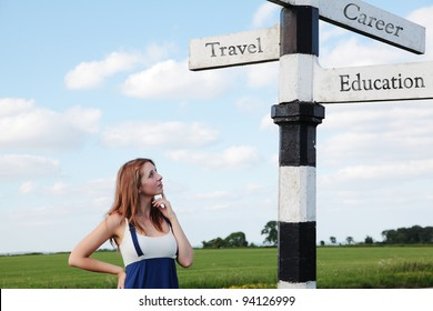A beautiful girl stood in front of a road sign highlighting the choices of Travel, Career and Education
