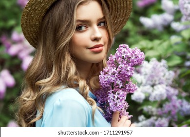 Beautiful girl in straw hat in lilac Garden. Girl with lilac flowers in springtime. Gardening.