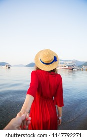 A beautiful girl in a straw hat and red dress is standing on the sea and holding her loved one's hand. Romance, happiness, love. Back view.