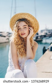 Beautiful girl in a straw hat rests against the backdrop of yachts